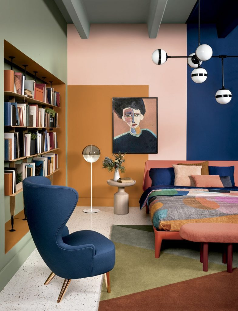 room with orange, green, blush and classic blue wall and mid century modern furniture