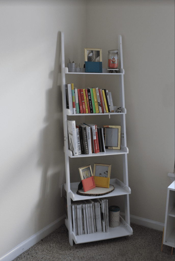 book shelf with magazines, books, gold frames, and candles