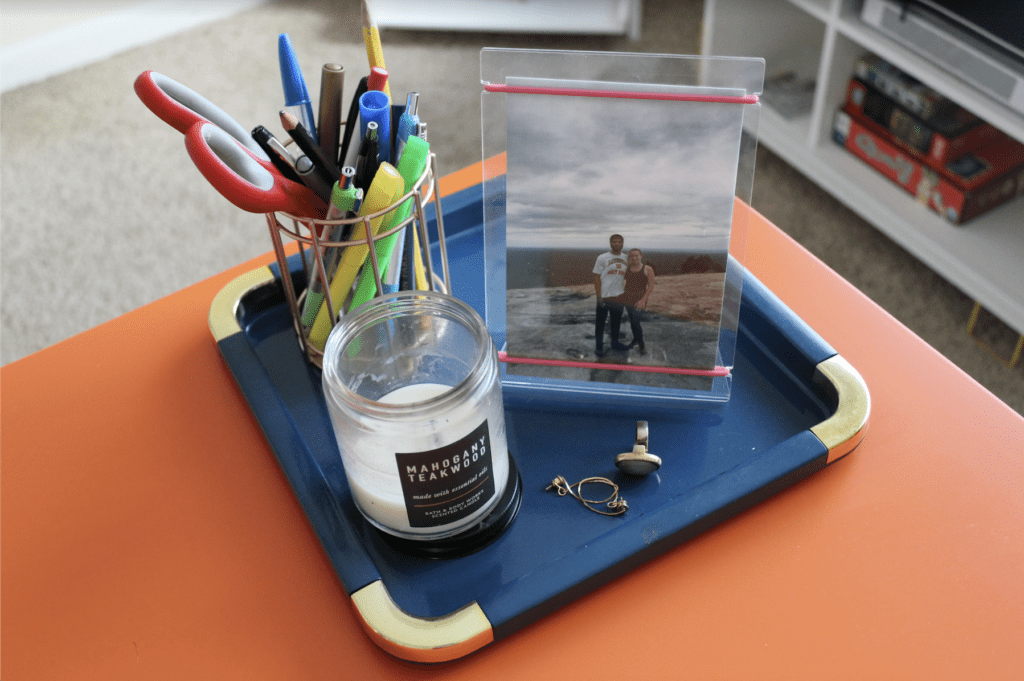 Teal tray on the corner of orange desk with gold pen holder, mahogany teakwood candle, framed photo of girl and man on mountain top, ring, and earrings