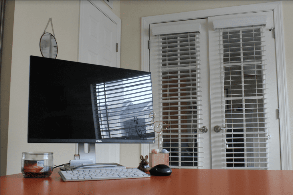 Monitor, keyboard, candle, and desk accessories. Small circular mirror on back left wall. French doors in the background