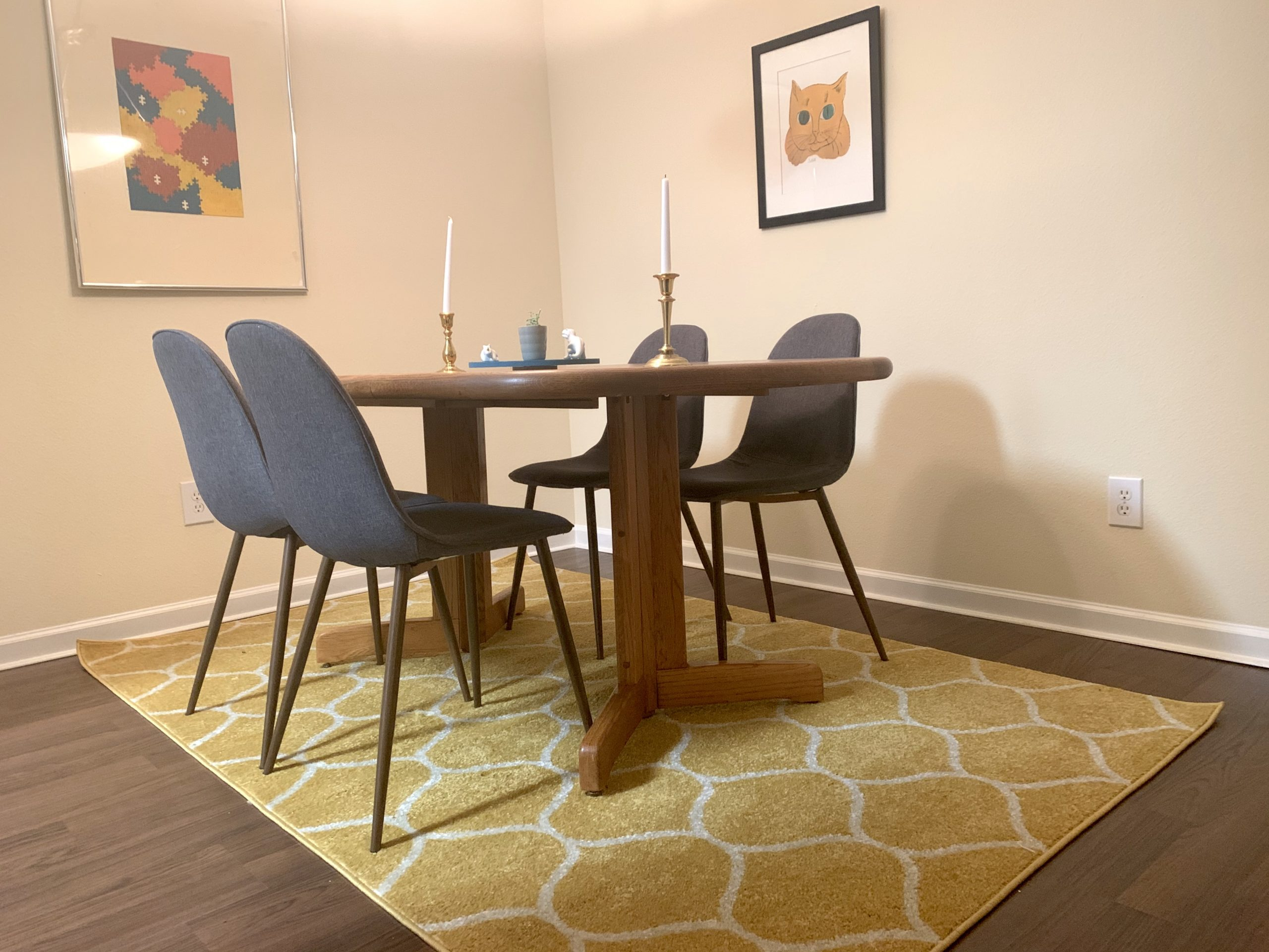 midcentury dining room with mustard yellow rug and abstract artwork on wall