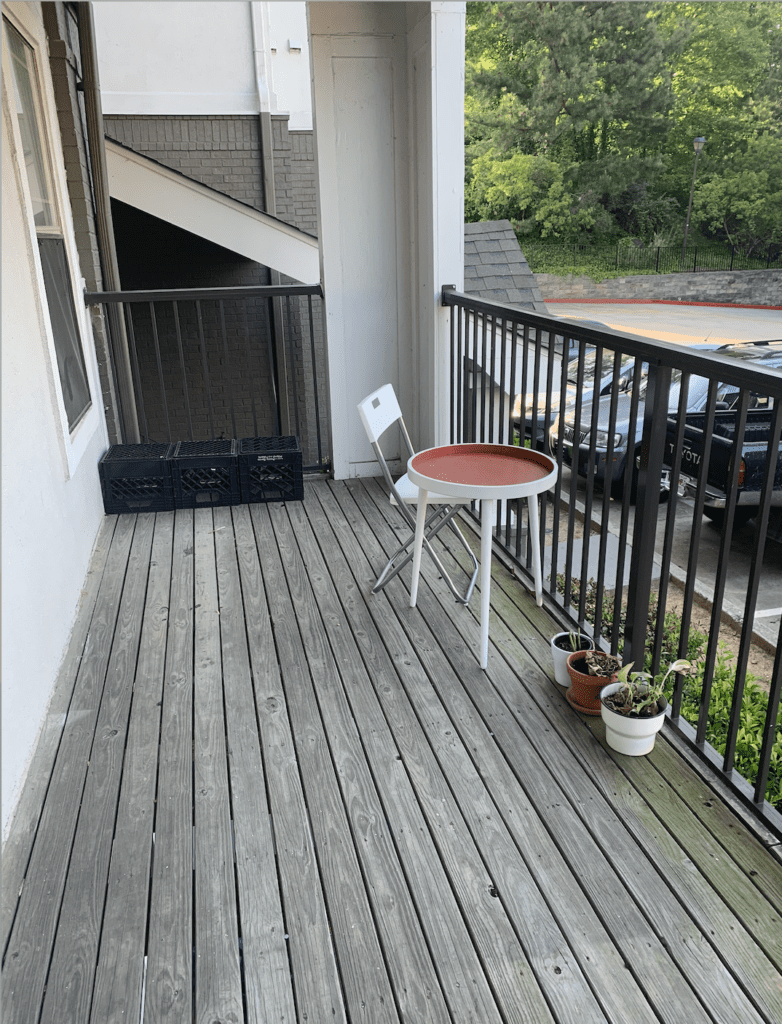 Undecorated balcony with milk crates, folding chair, small orange and white table, and plants on the ground