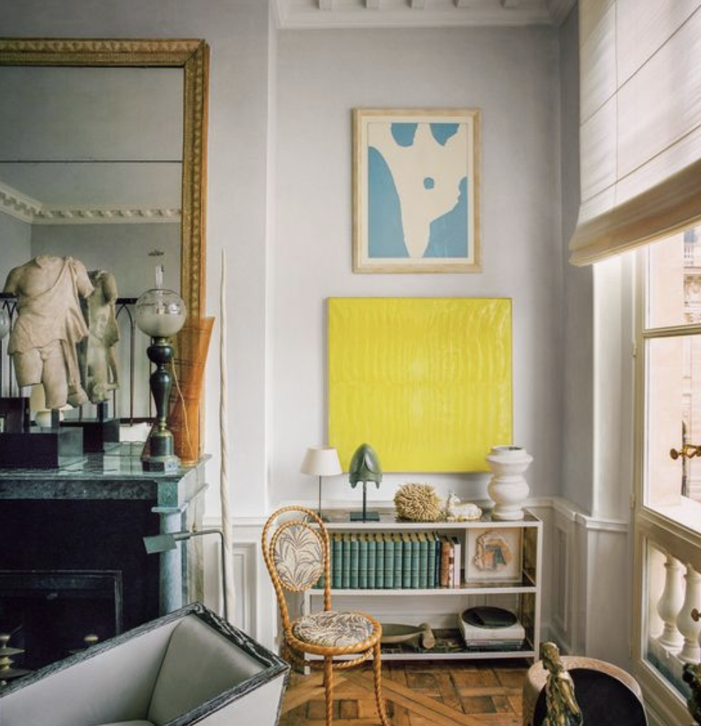 Gray walls with bright yellow piece of artwork on wall next to mantel and above short bookshelf