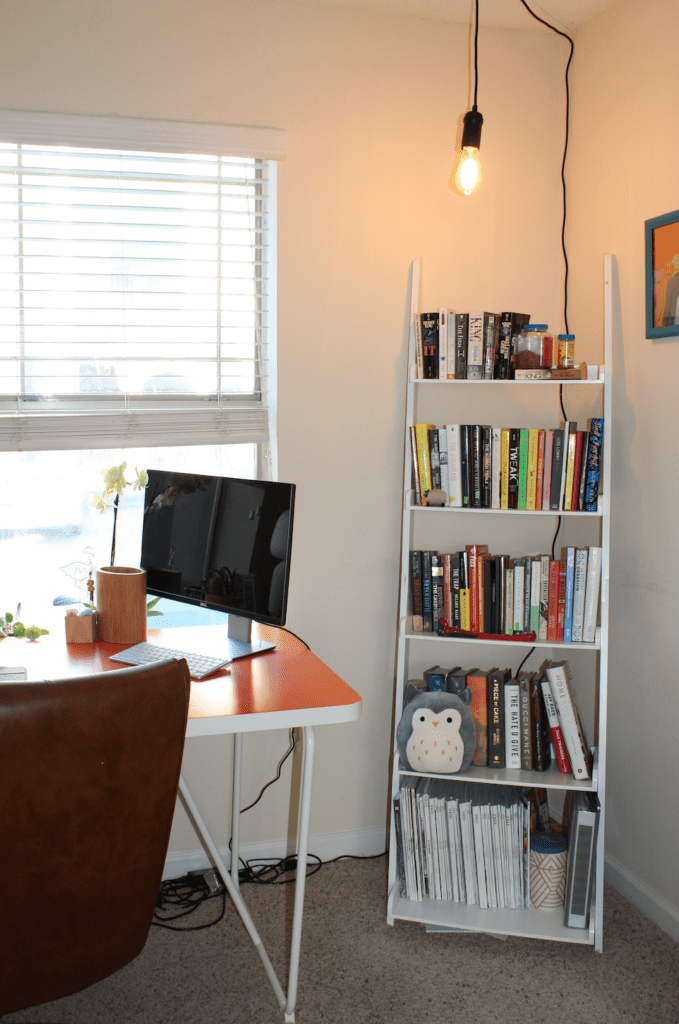 Corner of multipurpose office with a bookshelf and industrial pendant light