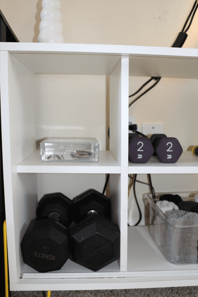 shelf with free weights, rolled up towels, and an acrylic drawer with hair supplies