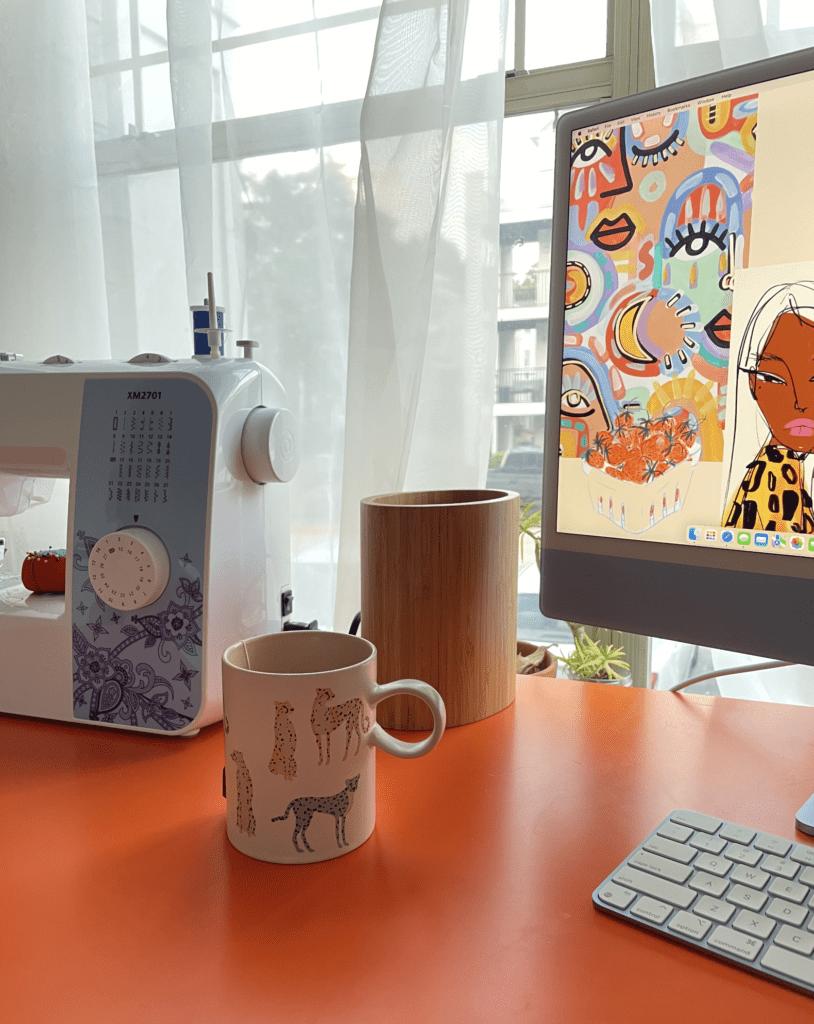 blue m1 iMac on orange desk next to sewing machine and a colorful giraffe mug