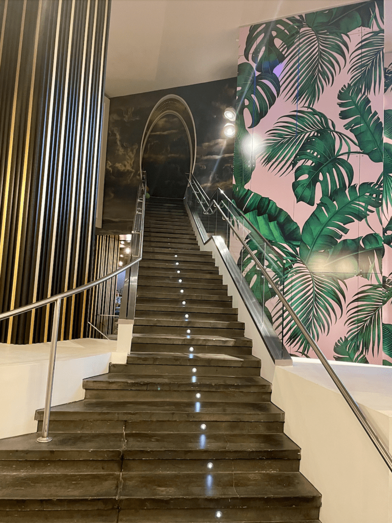 The W Atlanta hotel Midtown - stairs ascending beside pink and green palm leaf wallpaper