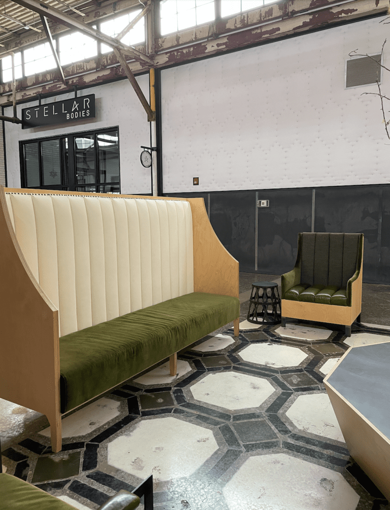 Olive green velvet, white faux leather, a and pale wood seating area with hexagonal tiles on floor - The Works ATL